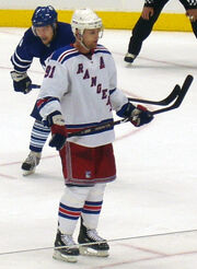 An ice hockey player skating on the ice. He wears a white jersey with black trim and is helmetless. He looks forward and holds his stick horizontally across his torso in a relaxed fashion.