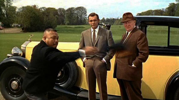 File:Goldfinger-oddjob-throws-hat-auric-sean-connery-bond.jpg