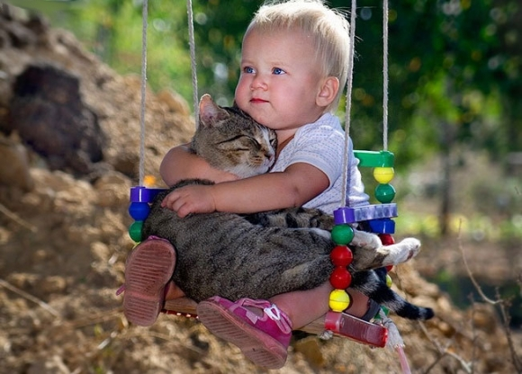 L-Just-a-baby-holding-a-kitten.-In-a-swing