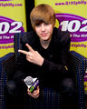 Justin making a peace sign at the Q102 radio station