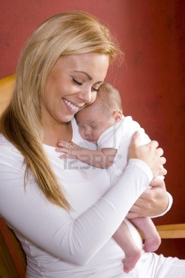 7018674-contemplative-young-mother-holding-newborn-baby-in-rocking-chair