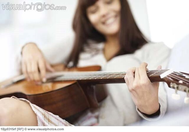File:Relaxed pretty young lady playing guitar 18jy0315rf.jpg