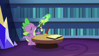 Spike blows magic fire on his scroll S6E15
