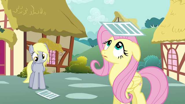 File:Fluttershy looking at newspaper on her head S2E22.png