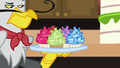 Gustave le Grand holding tray of jeweled cupcakes S5E10.png