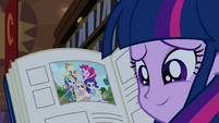 Twilight smiling with yearbook open EG