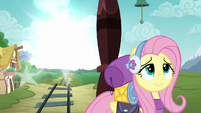 Fluttershy smiling while something appears in the distance S6E17