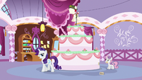 Rarity crosses in front of the giant cake S6E15