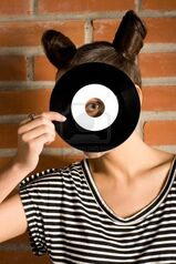 10102527-frau-mit-vinyl-platte-auf-mauer-hintergrund
