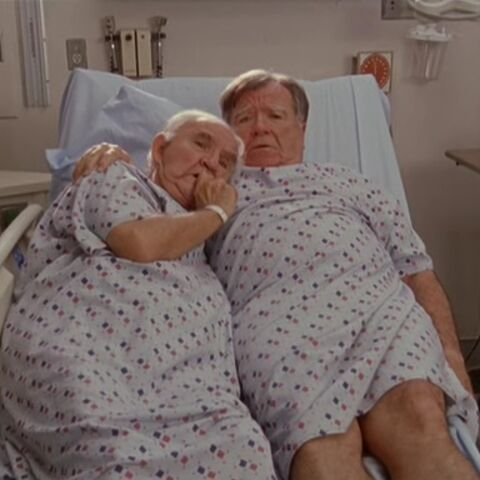 Two old male patients cuddle in one of the beds