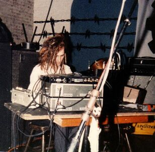 Alaric performing with '''Trial''', playing tape decks & signal processor. Mabuhay Gardens, San Francisco 1986