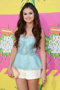 Selena holding a beige purse