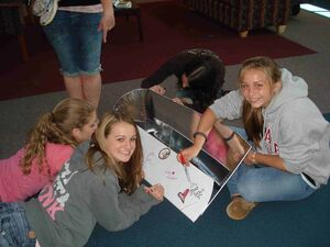 8th grade class signing plastic cookits in route to Sudan