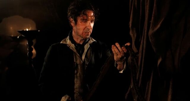 File:Eighth Doctor holds bandolier.jpg