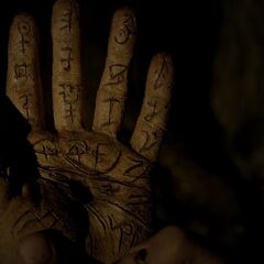 A rotting hand inscribed with gliphs