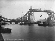 A black and white photograph of the Tower Bridge during its construction.