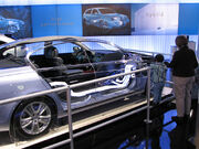 Cutaway hybrid car showing electrical connections; auto show display backdrop.
