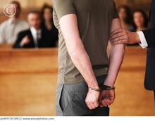 Handcuffed man standing in courtroom pe0073747