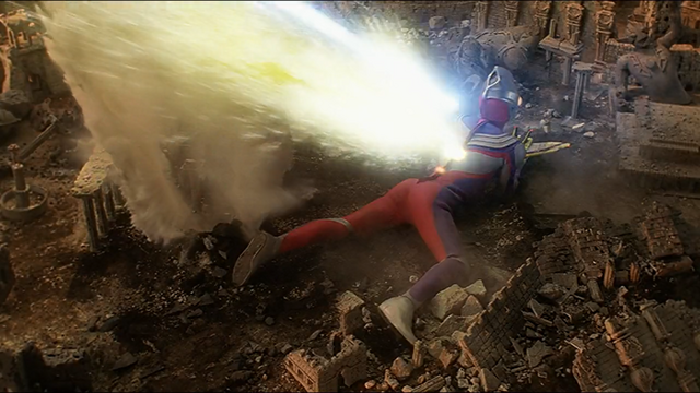 File:Daigo (Tiga) protects Rena by his own body.png