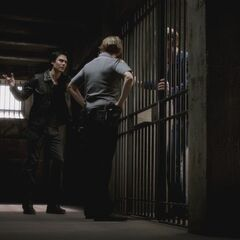 Alaric in a prison cell, with Damon arguing with Forbes that Ric isn't the murderer