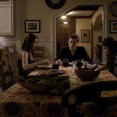 Same angle, but now we can see the kitchen table. The front door is behind Stefan