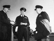 Informal portrait of three men in dark military uniforms with peaked caps