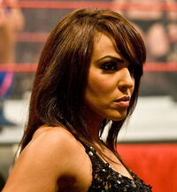 A close-up headshot of a tanned, Caucasian woman with brown hair, slightly past shoulder length, who is wearing a black top.