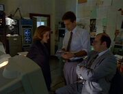 Charles Burks watches Fox Mulder and Dana Scully
